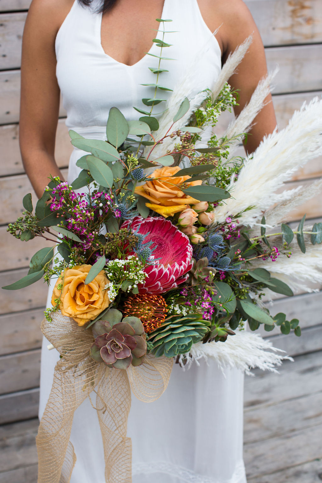 extra large boho style succulent bouquet featuring proteas, feathers, and pampas grass by Succulents for Hire